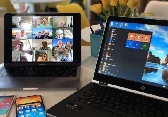Kaksi kannettavaa tietokonetta, toisen näytöllä näkyy videokonferenssi.