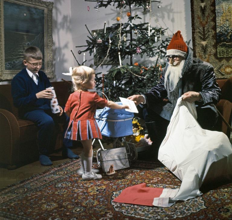 Joulupukki ojentaa pikkutytölle lahjapakettia. Vieressä sohvalla tytön isoveli avaa omaa pakettiaan.