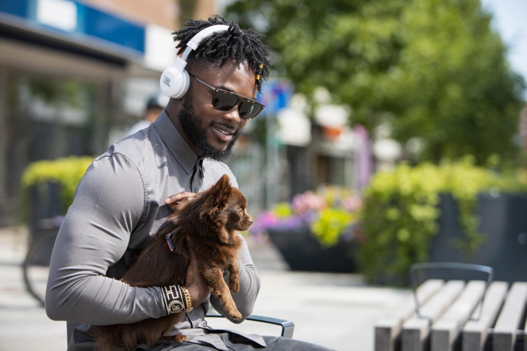 Nuori musta mies istuu penkillä kuulokkeet korvillaan ja pieni ruskea koira sylissään. Taustalla katumaisema.